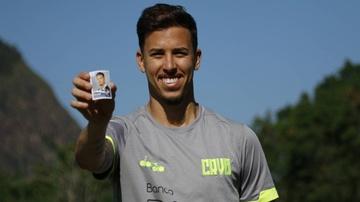 Marcos Junior segura figurinha de futebol com seu rosto